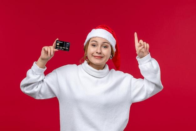 Jovem mulher sorridente segurando o cartão do banco sobre fundo vermelho.