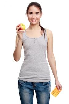 Jovem mulher sorridente segurando o comprimido em uma mão ee maçã em outro