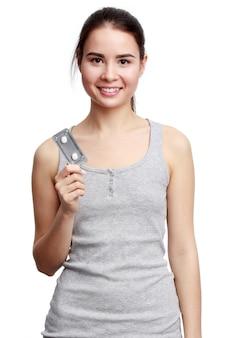 Jovem mulher sorridente segurando remédios nas mãos