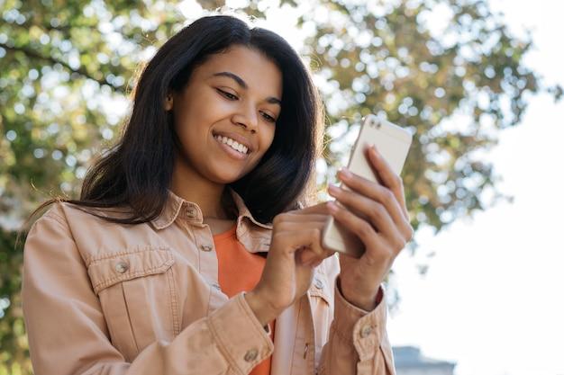 Jovem mulher sorridente segurando smartphone, conversando, comunicação, olhando para a tela digital
