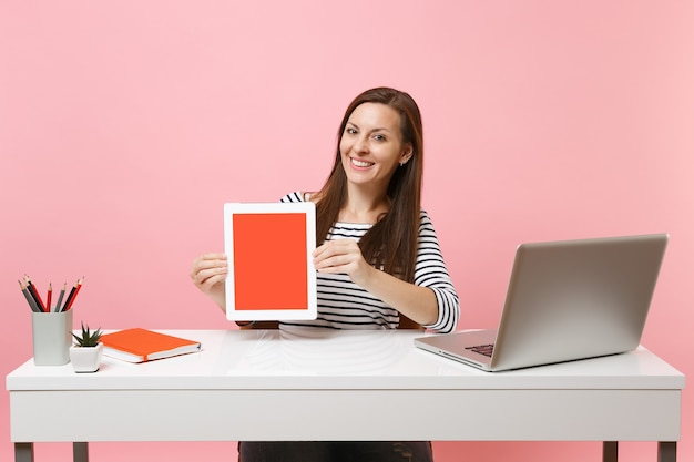 Jovem mulher sorridente segurando um computador tablet com a tela em branco e vazia, sente-se no trabalho na mesa branca com um laptop pc contemporâneo