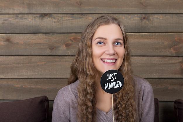 Jovem mulher sorridente segurando um ícone engraçado em uma vara com a inscrição de recém-casado