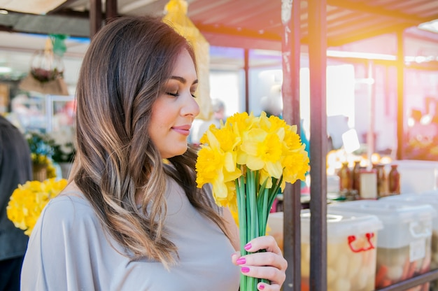 Jovem, mulher sorridente selecionando flores frescas. feche o retrato do perfil de uma bela e jovem curtindo um buquê de flores enquanto estiver em uma barraca de mercado floral fresca durante um dia ensolarado ao ar livre.