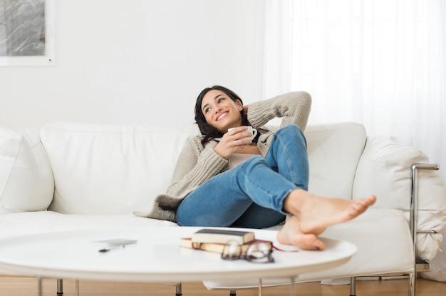 Jovem mulher sorridente, sentada no sofá e olhando para cima enquanto bebe chá quente