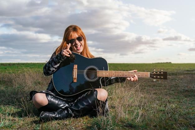 Jovem mulher sorridente sentada tocando violão no campo ao pôr do sol com céu e nuvens