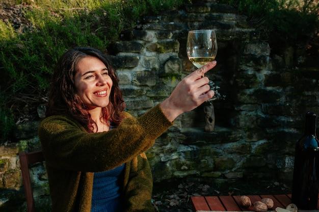 Jovem mulher sorridente, sentado em um jardim, tomando um aperitivo com vinho.