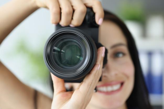 Jovem mulher sorridente tirando fotos na câmera profissional preta.