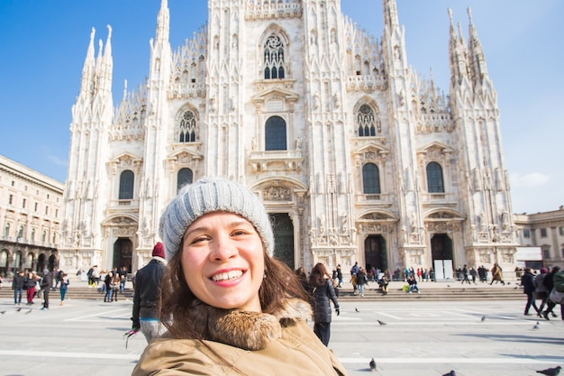 Jovem mulher sorridente tirando uma selfie em frente ao duomo da catedral de milão