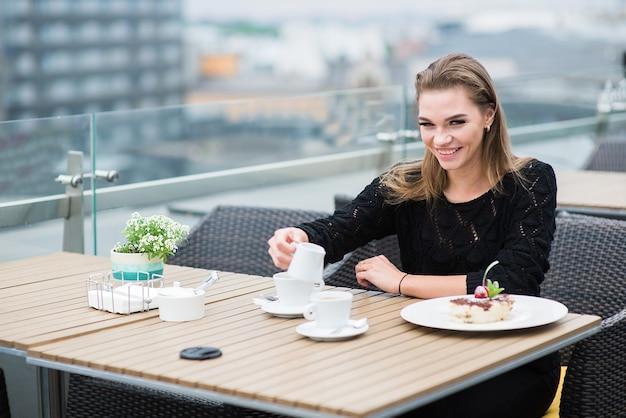 Jovem mulher sorridente tomando café da manhã no terraço ao ar livre do hotel