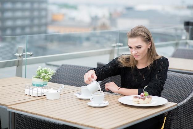 Jovem mulher sorridente tomando café da manhã no terraço ao ar livre do restaurante do hotel