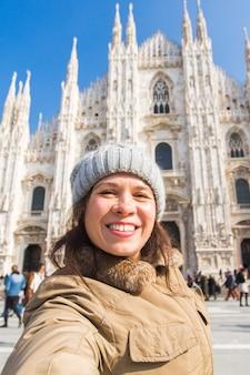 Jovem mulher sorridente tomando selfie em frente à catedral de milão duomo di milano, itália.