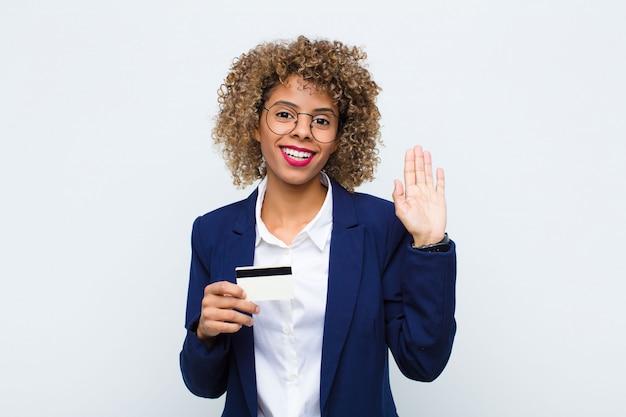 Jovem mulher sorrindo alegremente e alegremente, acenando com a mão, dando as boas-vindas e cumprimentando-o ou dizendo adeus com cartão de crédito