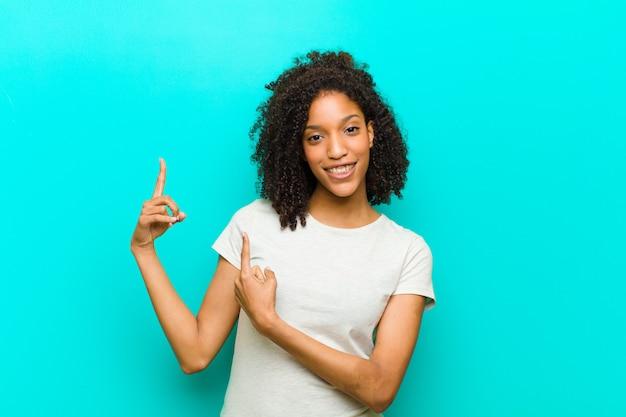 Jovem mulher sorrindo alegremente e apontando para o lado e para cima com as duas mãos, mostrando o objeto no espaço da cópia sobre parede azul
