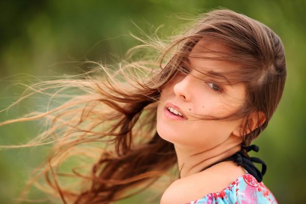 Jovem mulher sorrindo com cabelo varrido pelo vento