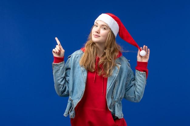 Jovem mulher sorrindo com tampa vermelha sobre fundo azul, ano novo, férias natal, vista frontal