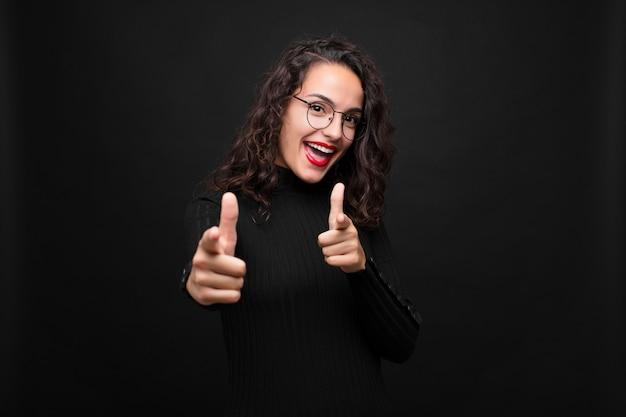 Jovem mulher sorrindo com uma atitude positiva, bem-sucedida e feliz apontando, fazendo sinal de arma com as mãos no preto.