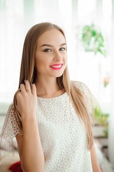 Jovem mulher sorrindo e olhando para a câmera