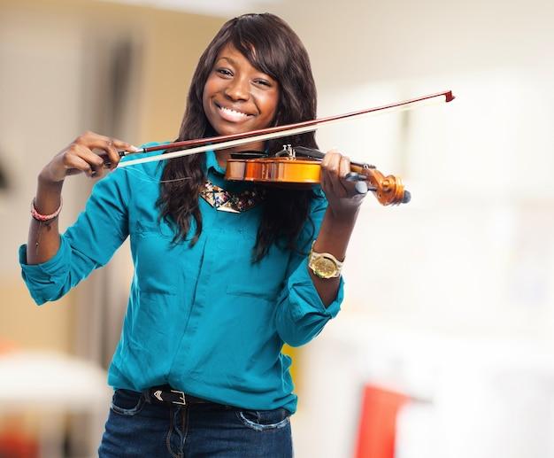 Jovem, mulher, sorrindo, enquanto a tocar violino