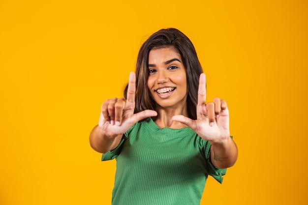 Jovem mulher sorrindo fazendo moldura com as mãos e os dedos com uma cara feliz. criatividade e conceito de fotografia.