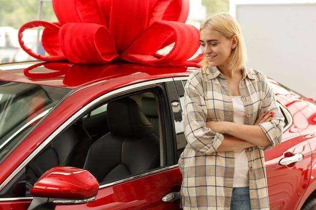 Jovem mulher sorrindo olhando para o novo automóvel com um grande laço vermelho no telhado.