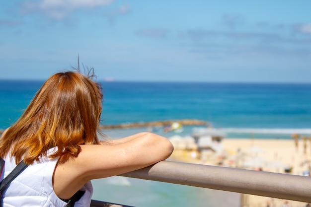 Jovem mulher sozinha na varanda em frente à praia do mar. imagem para paisagem, natureza, viagens, pessoa.