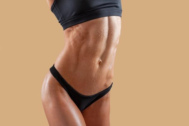 Jovem mulher super do ajuste bonito que mostra fora seu abs rasgado muscular perfeito.