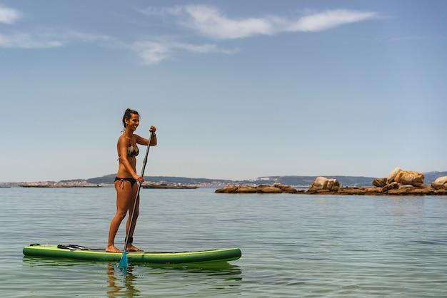 Jovem mulher surfando uma prancha no oceano