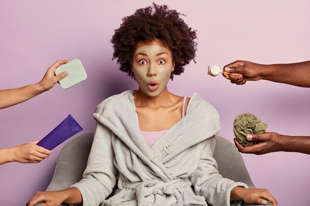 Jovem mulher surpresa cuida da pele, limpa os poros com máscara facial de lama, veste roupão doméstico, olha com expressão de omg