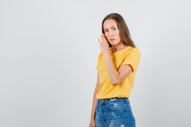 Jovem mulher sussurrando segredo por trás das mãos em uma camiseta, shorts e parecendo séria