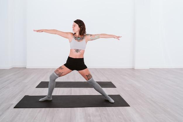 Jovem mulher tatuada praticando esporte de ioga na academia