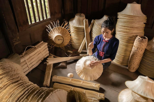 Jovem mulher tecendo cesta artesanal