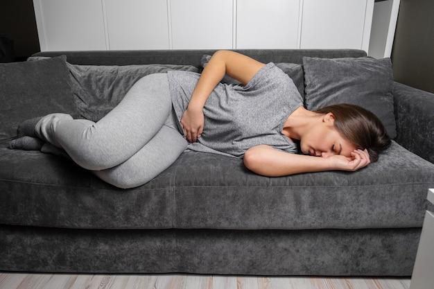 Jovem mulher tem dor de estômago deitado no sofá