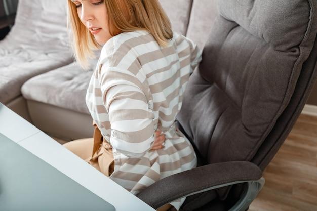 Jovem mulher tem dor nas costas, sentado na cadeira do escritório. dor aguda no músculo espinhal do pescoço na região lombar durante o trabalho em casa. trauma de doença da coluna vertebral. adolescente com escoliose, problemas do nervo espinhal comprimido.