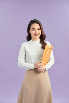Jovem mulher tem nas mãos um envelope amarelo, pacote, entrega de compra, envelope de correio. perfil.