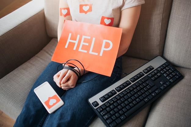 Jovem mulher tem vício em mídias sociais. as mãos estão embrulhadas com cordão. teclado ao lado. ajuda papel. dependência do laptop ou smartphone. cortar vista.