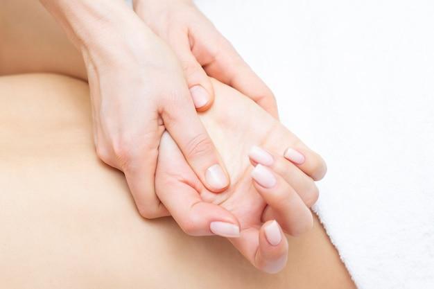 Jovem mulher tendo braço massagem no salão.