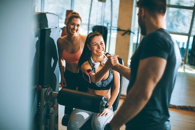 Jovem mulher tendo exercícios na extensão da perna e máquina de enrolar as pernas no ginásio