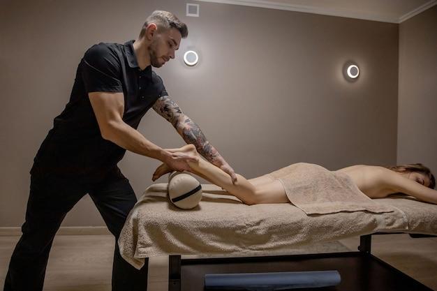 Jovem mulher tendo massagem nos pés no salão de beleza, close-up vista.