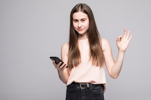 Jovem mulher tendo uma conversa falando no smartphone sobre parede isolada, fazendo sinal de ok com os dedos