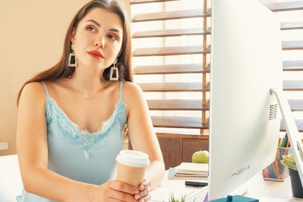 Jovem mulher tendo uma pausa para café enquanto está sentado em seu escritório