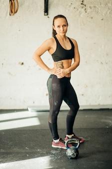 Jovem mulher tendo uma pequena pausa no seu treino de fitness kettlebell