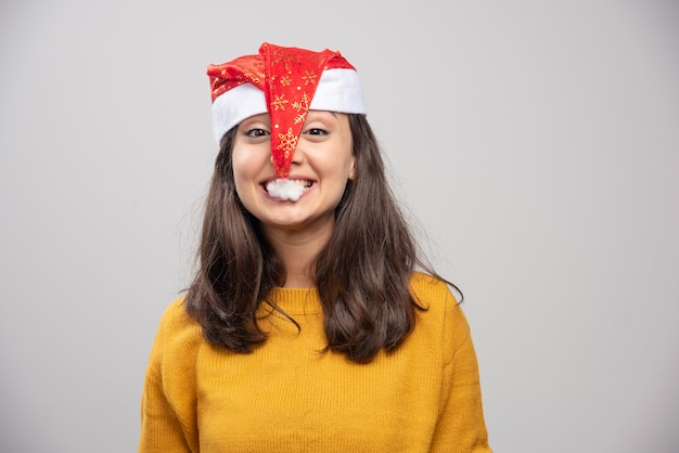 Jovem mulher tentando comer o chapéu vermelho de papai noel.