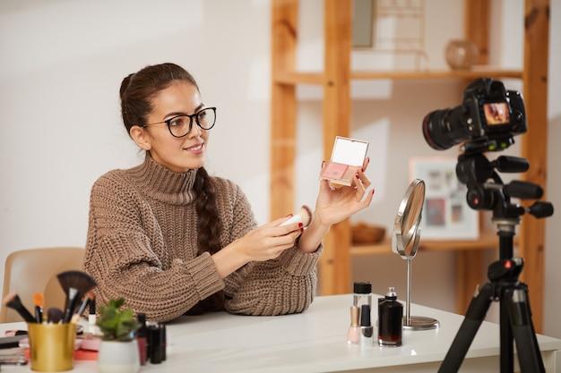 Jovem mulher testando produtos de beleza para vídeo