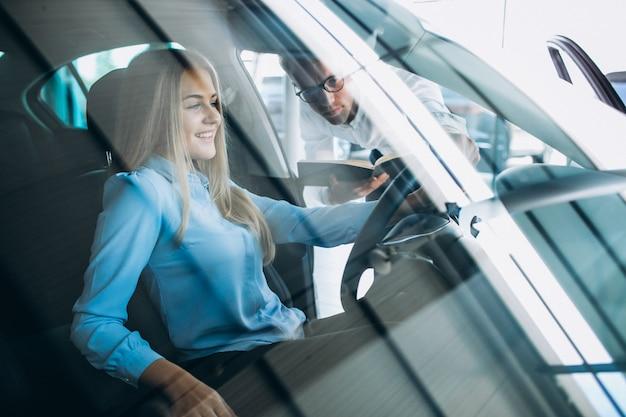 Jovem mulher testando um carro em uma sala de exposições