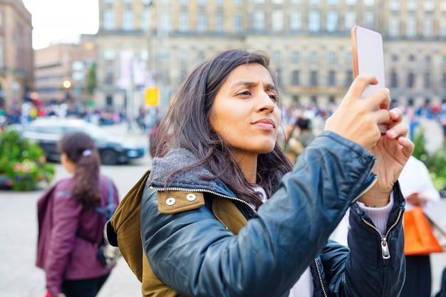Jovem mulher tirando foto da cidade