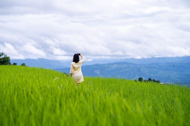 Jovem mulher tirando foto de paisagem montanhosa.