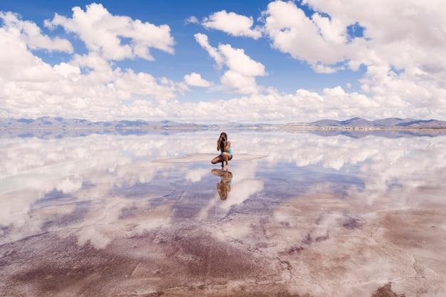 Jovem mulher tirando foto de reflexo de água bonita