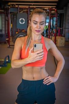 Jovem mulher tirando foto de selfie pelo espelho após o exercício na academia
