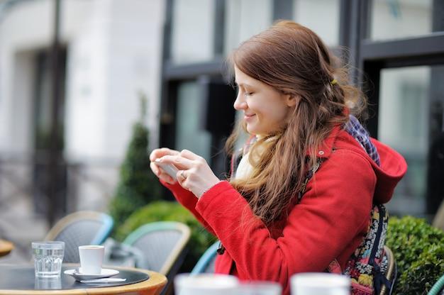Jovem mulher tirando foto móvel de sua xícara de café em um café de rua parisiense