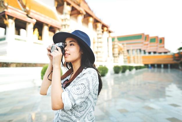 Jovem mulher tirando foto pela câmera de filme